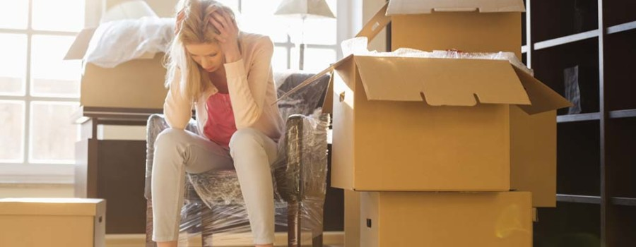 Full-length of frustrated woman sitting by cardboard boxes in new house; Shutterstock ID 225491440; PO: Cat Overman; Job: blog post